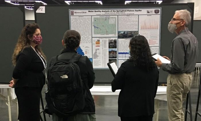 People looking at a poster presentation of data from research.