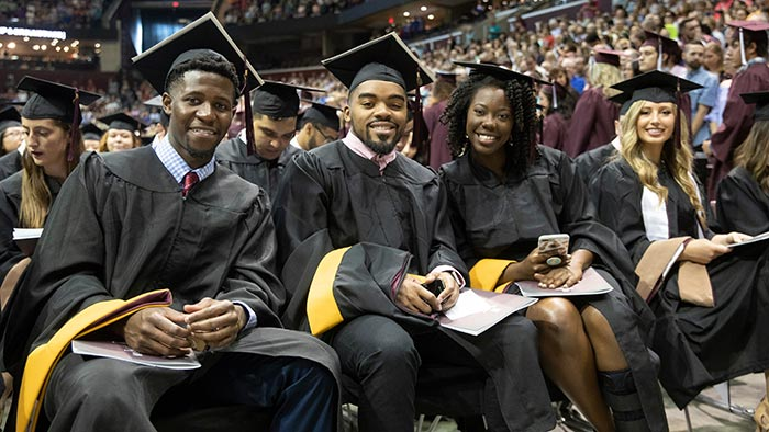 Howard Scarborough with friends at graduation.
