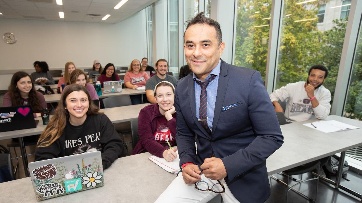 Dr. Albert Barreda with students in classroom. (Photo taken in 2018.)