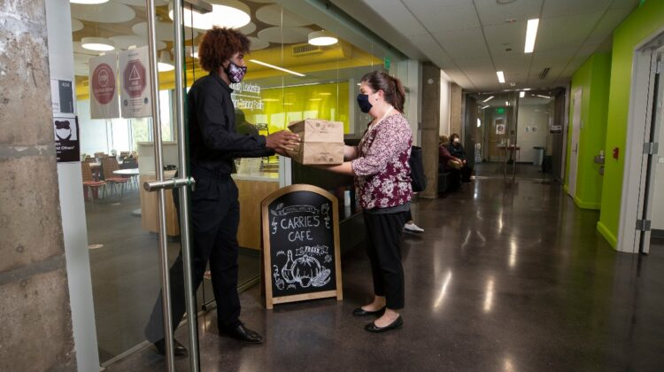 Carrie's Cafe student employee delivers carryout order to customer.