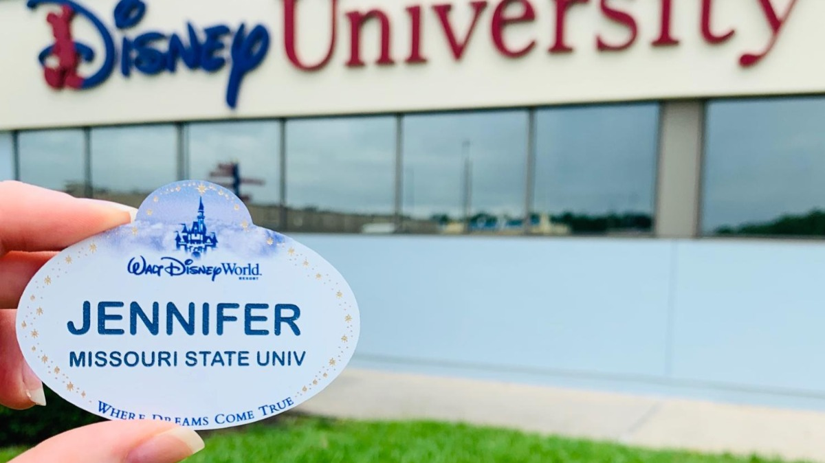 Jennifer Johnson holds up her Disney name tag in front of Disney University facility.