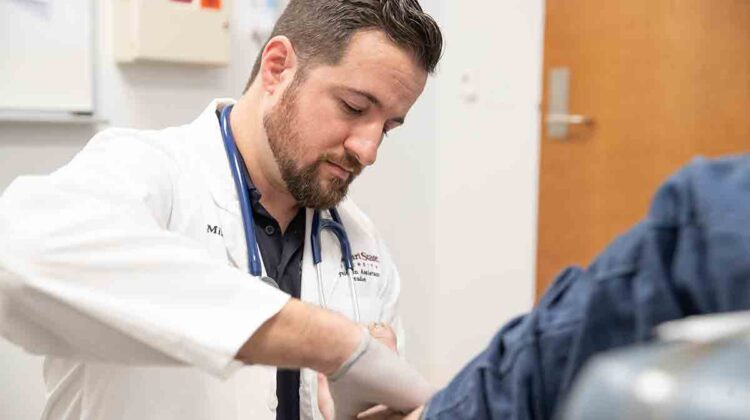 Mikel Dashtipour works with patient in MSU Care Clinic