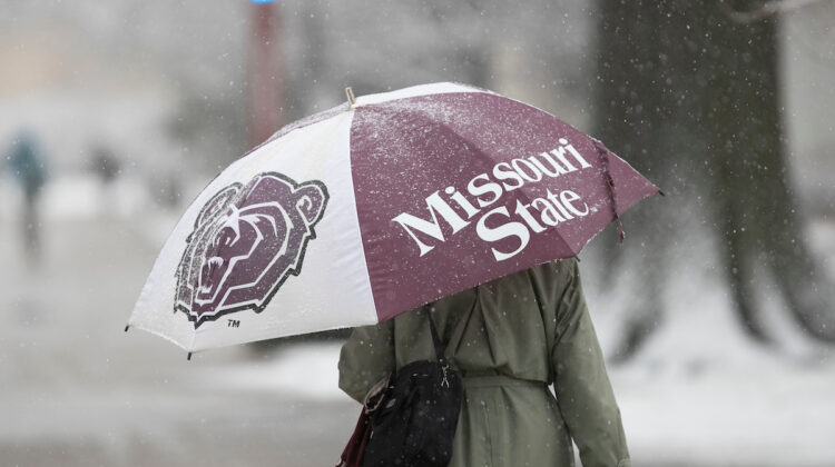 Lady walks underneath MSU umbrella while snowing