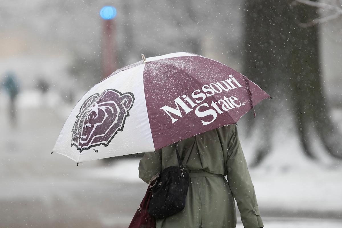 Lady walks underneath MSU umbrella while snowing