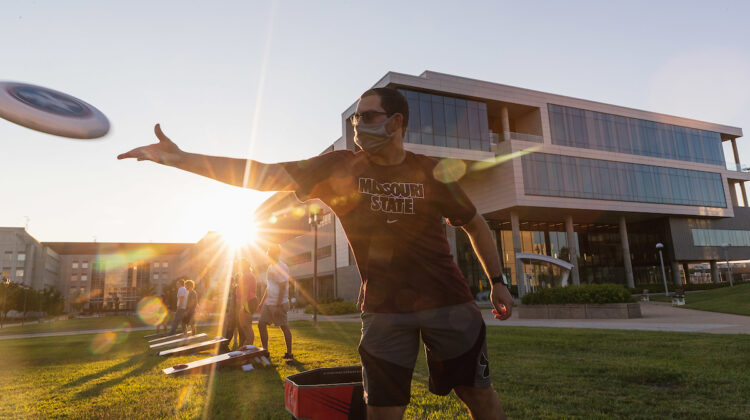 Masked student throws frisbee as sun sets behind Glass Hall.