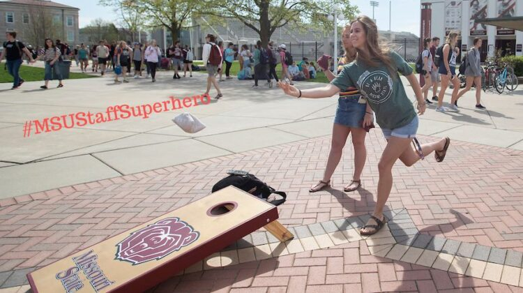 Student throws bean bag in game of corn hole on campus.