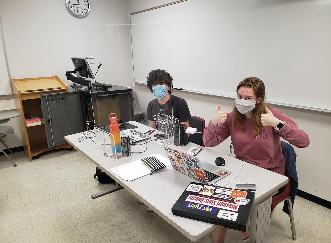 Photo of two debate team members sitting at a desk (Photo Credit: Eric Morris)
