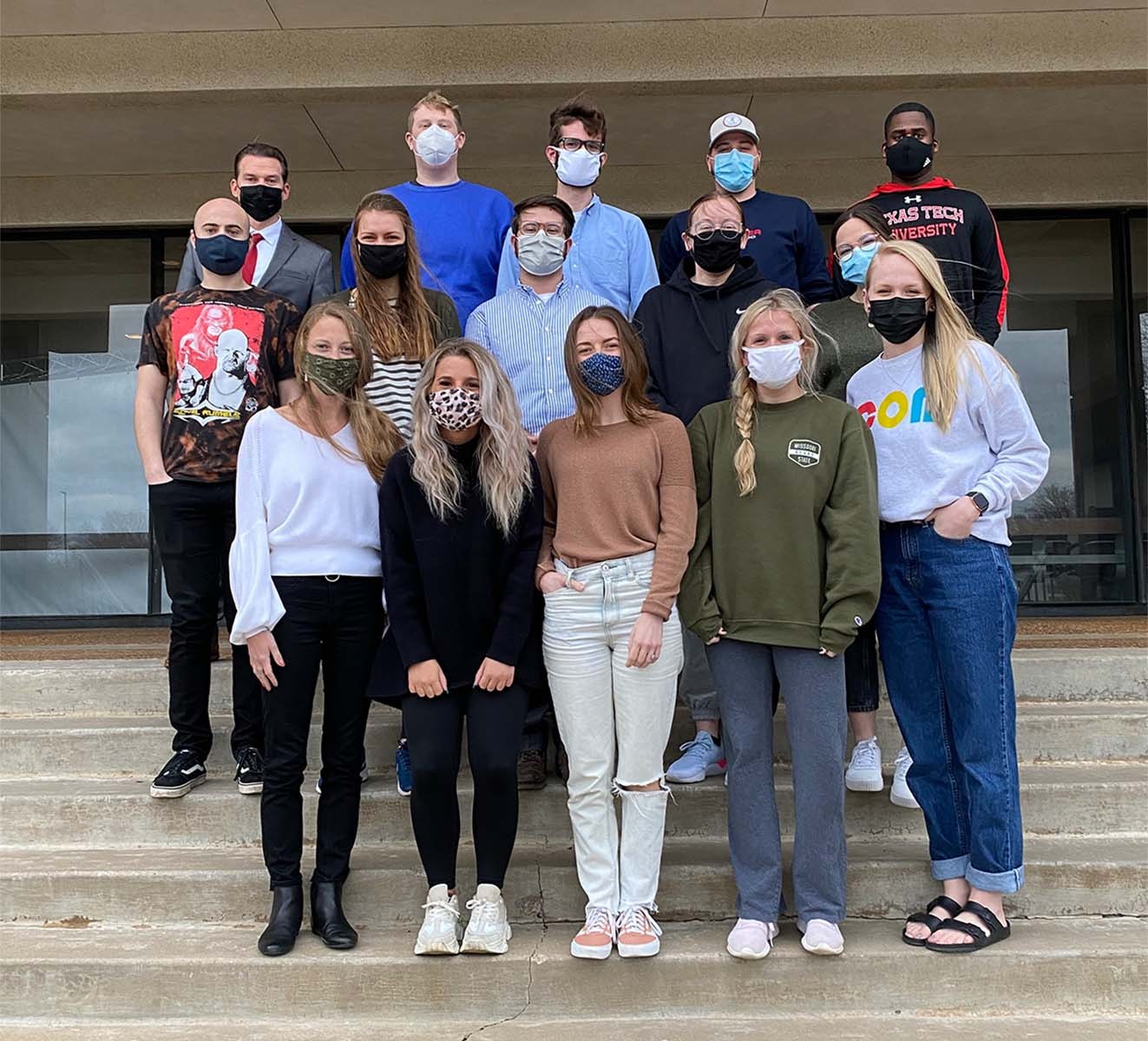 Photo of a group of graduate communication students in masks on a staircase (Photo Credit: Carissa Hoelscher)