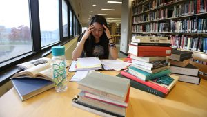 A student stressing over books in Meyer Library.