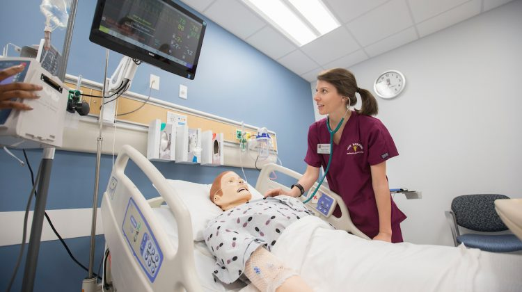 A nursing student attends to a simulated scenario