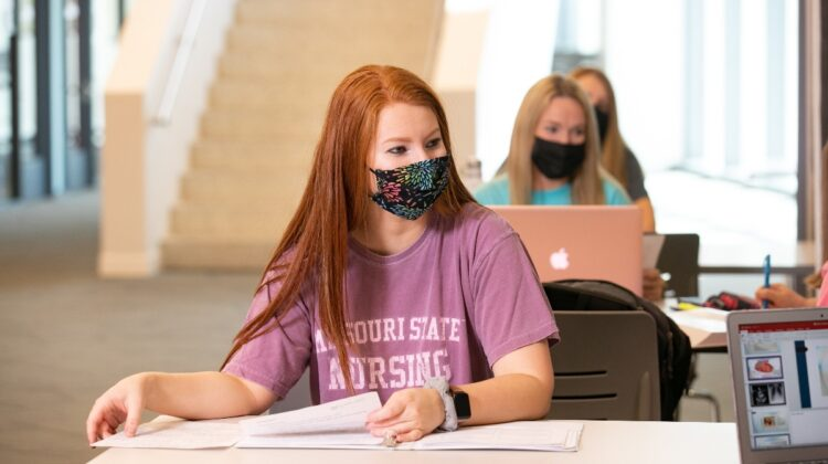Student studies while wearing mask.