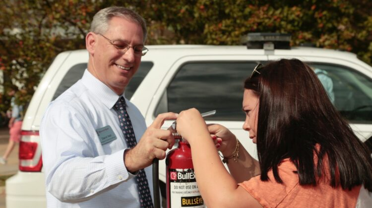 David Hall teaches student how to use fire extinguisher.
