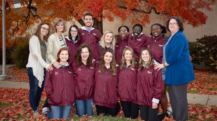 Glaessgen with 2018 Peer Leaders evening group in front of fall foliage.