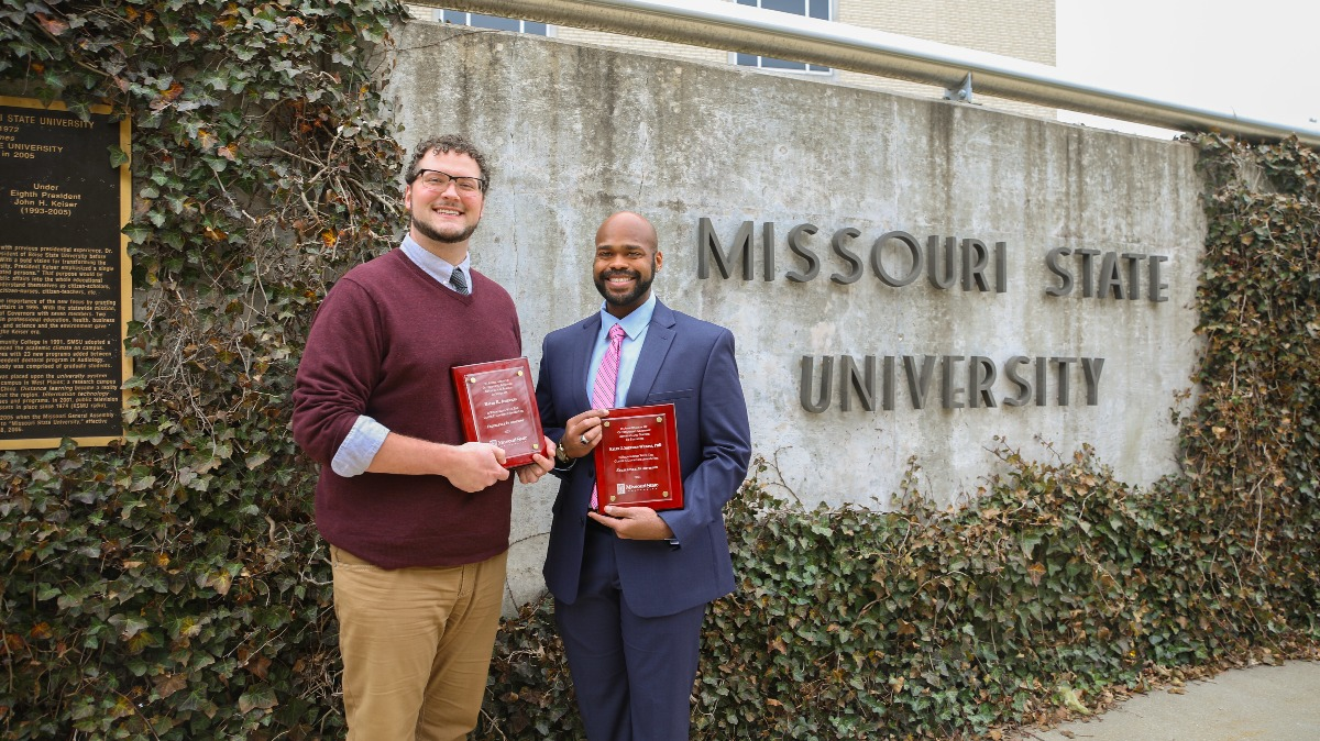 Dr. Kyler Sherman-Wilkins and David Johnson stand with their advising awards.