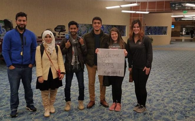 Students posing for a photo at airport arrival gate.