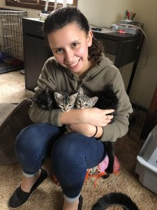 Gabriela Rivero holding four foster kittens