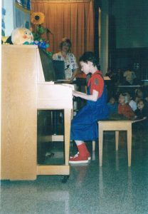 Girl playing piano for audience