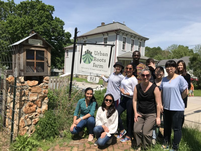 Listening students pose with English Language Institute instructor Cali Pettijohn near the Urban Roots Farm sign on a sunny day.