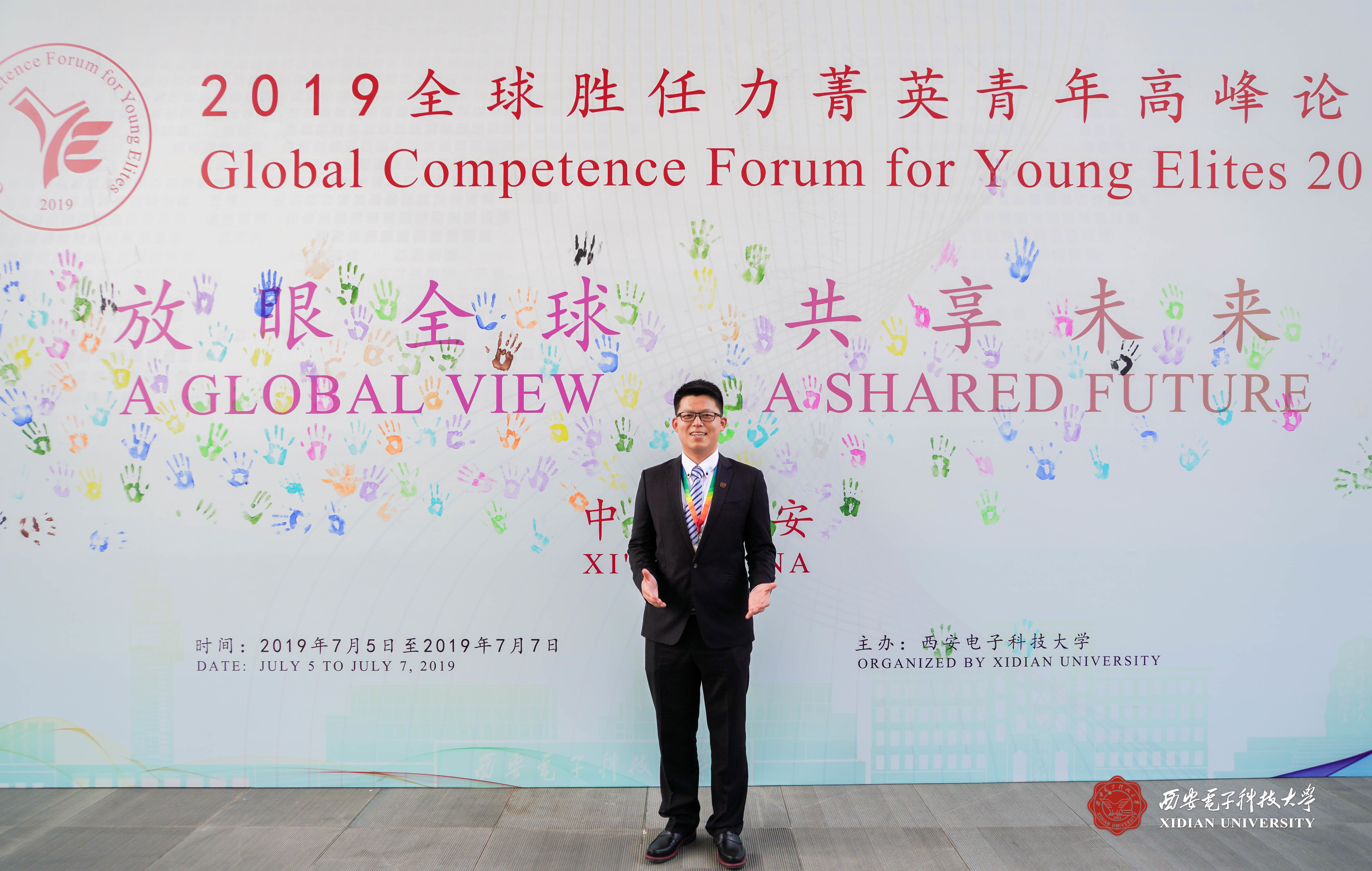 Allen Sun poses in front of a large poster about the Forum.
