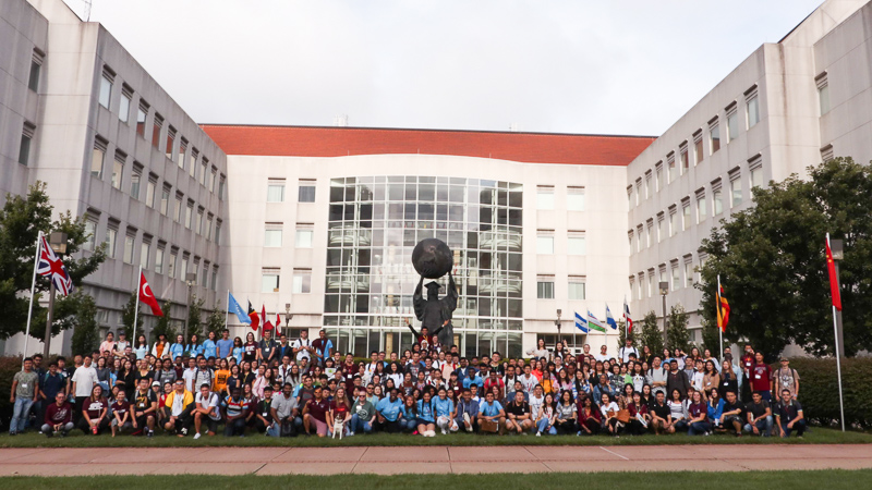 All new international student orientation attendees, volunteers, and staff in front of the citizen scholar bronze statue, a female figure in academic robes holding up the globe