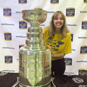 LOGOS Copy Editor for Volume 13 Emma Bishop poses with the Stanley Cup wearing St. Louis Blues gear