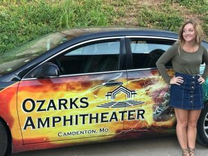 Maddy in front of an Ozarks Amphitheater car.