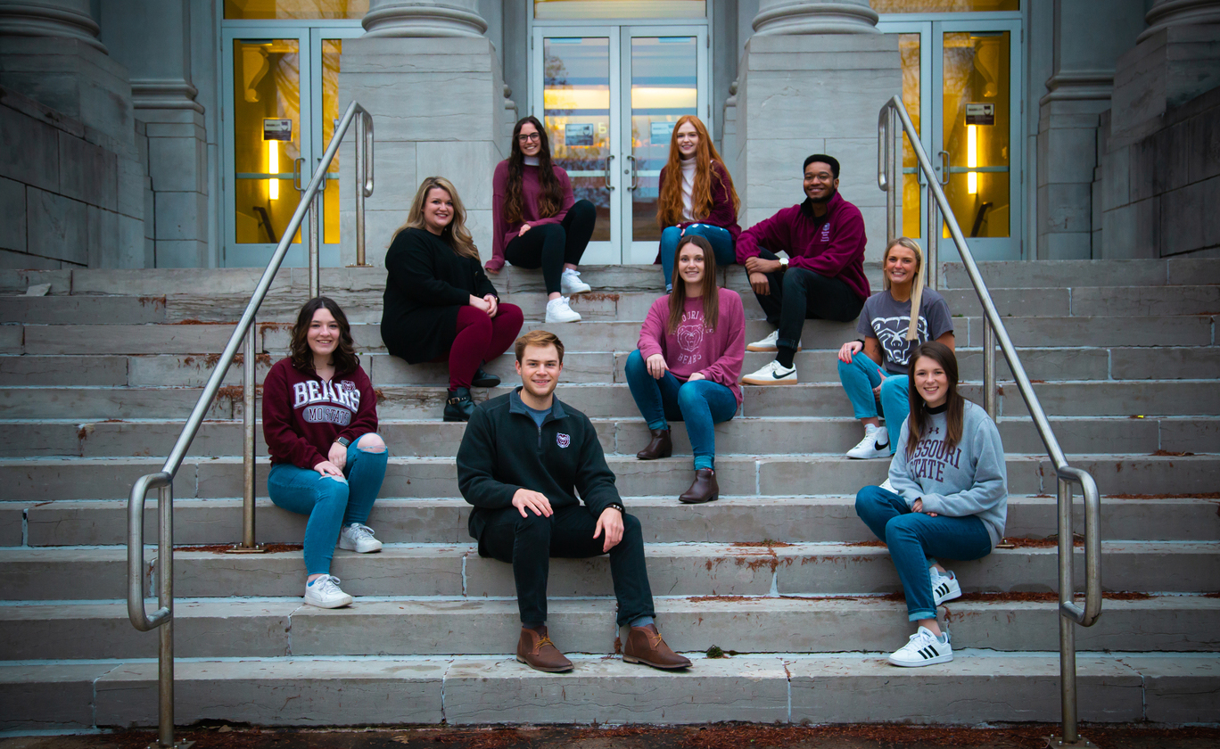 Members of the 2021 MSU Ad Team sit on the steps of Carrington Hall