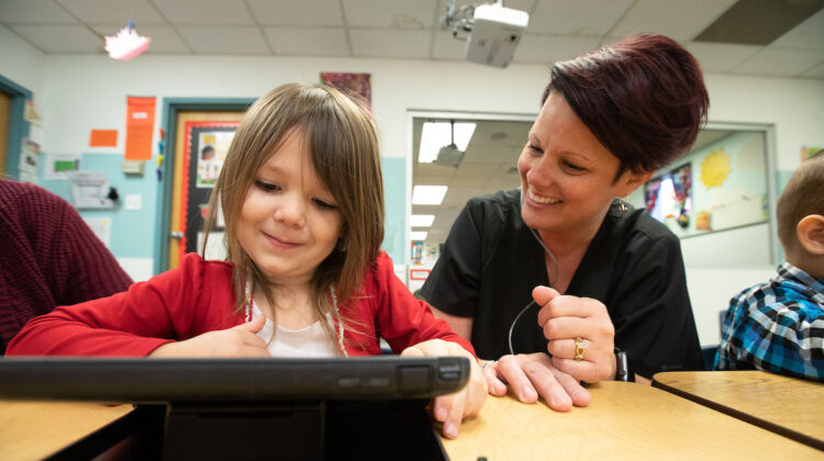 Tara Oetting helps a young girl on a screen device