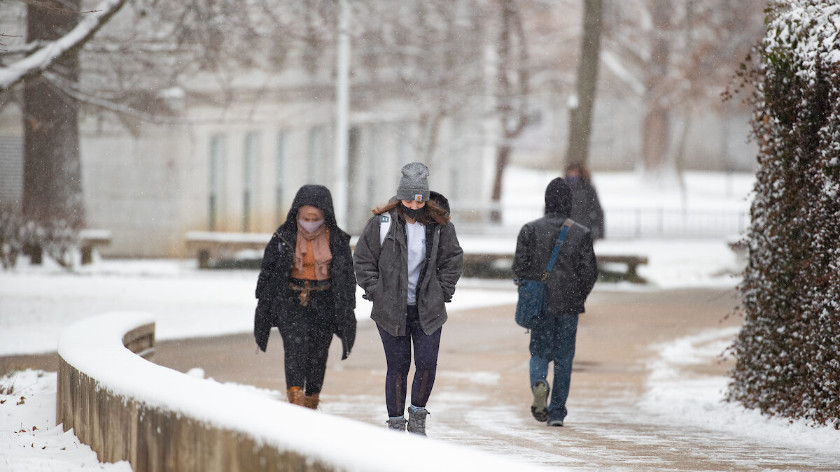 students walk in the snow on campus