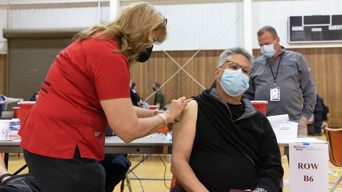 Man receives vaccine from nurse