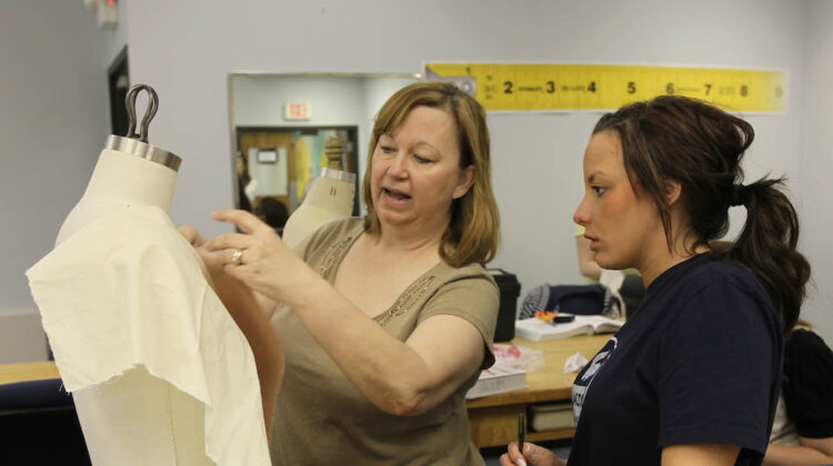 Teacher showing student how to lay fabric on mannequin.