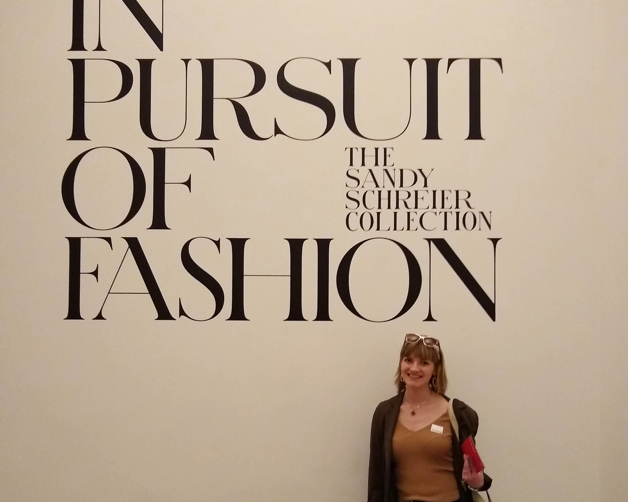 "Girl in front of wall that reads, ""In pursuit of fashion."""