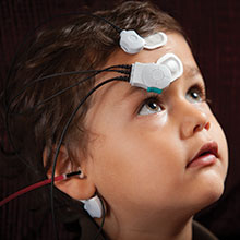 Luke Wilson, 3, is given a hearing screening by Dr. Wafaa Kaf. The electrodes measure his brain's responses to sounds.