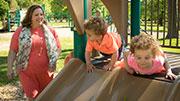 Dr. Brigden next to children on a slide