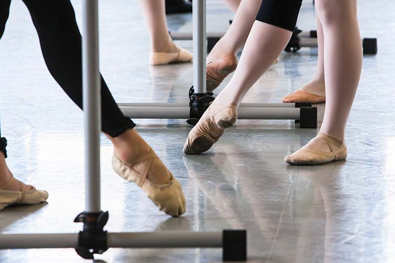Line of ballet dancers practicing pointe technique