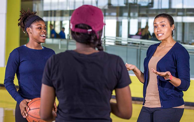 Dr. Perkins talks with two students on the basketball court inside Foster Recreation Center