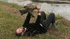 Dr. Ligon laying on ground holding a turtle in the air