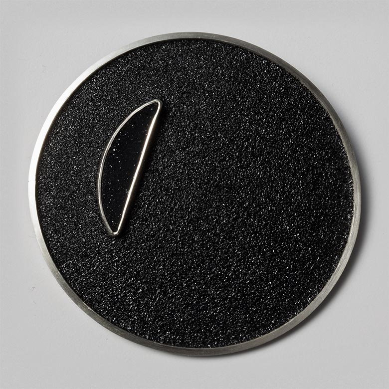 Black crescent-on-black circular field brooch