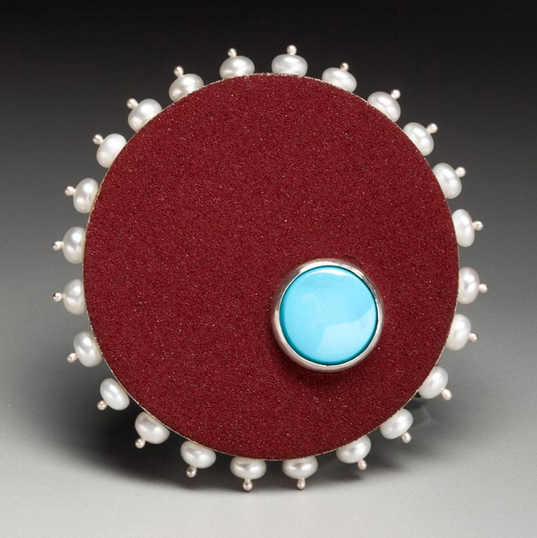 Red brooch with light blue accent and pearl-studded rim
