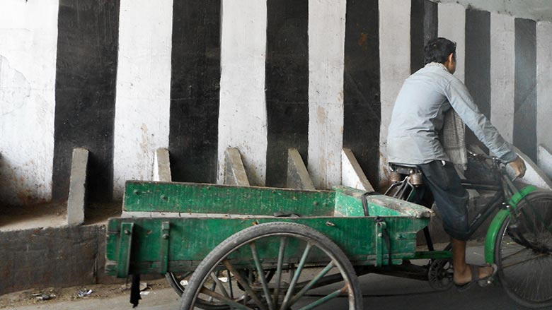 Delhi cart driver in front of striped wall pattern
