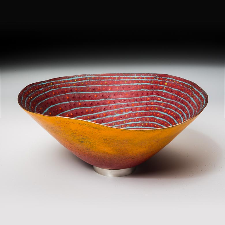 Orange bowl with silver and red spirals on the interior
