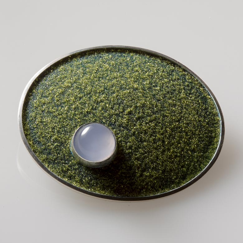 Oval brooch with glass accent on green field