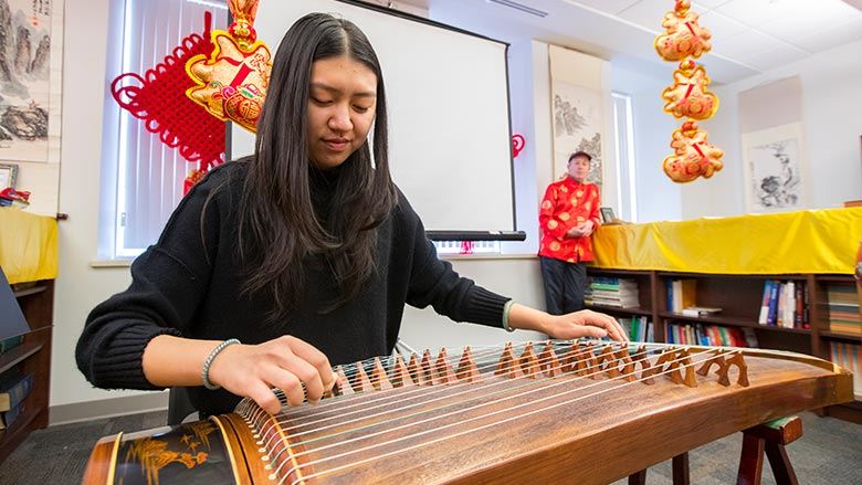 Student playing a traditional Chinese instrument
