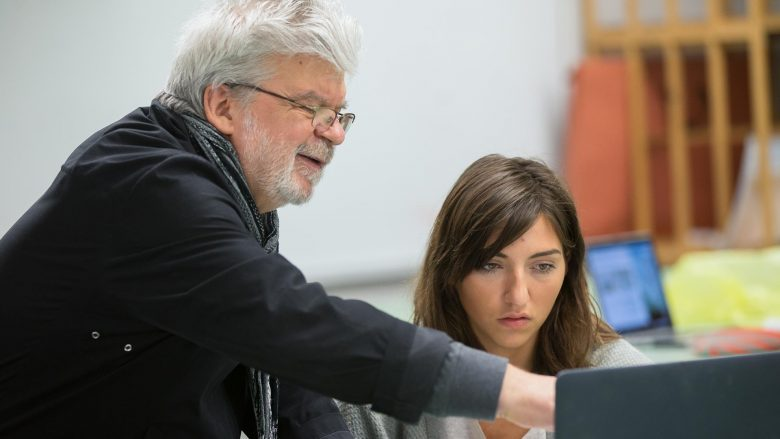 Cedomir Kostovic reviewing designs on a laptop with a student