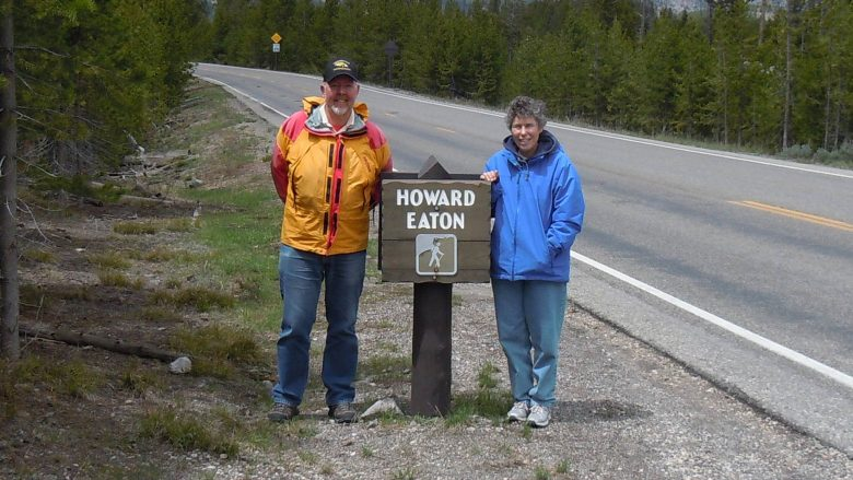 Leslie Quinn and Judith Meyer standing next to Howard Eaton Trail sign at Yellowstone National Park.