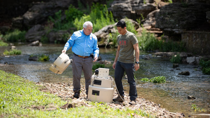 Dr. Gouzie working with a graduate student to collect water and sediment from local caves.