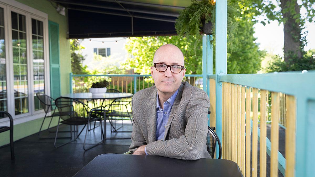 John Schmalzbauer sits on the Potter's House porch