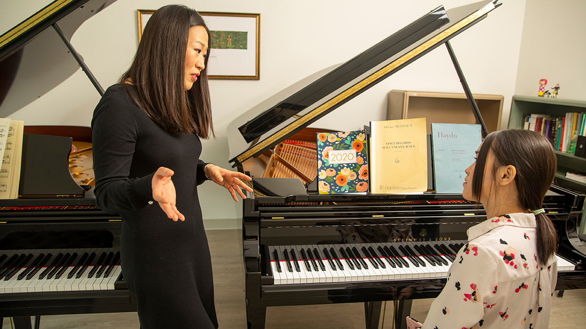 In her office, Minju Choi Witte provides instruction to an MSU student seated at a piano