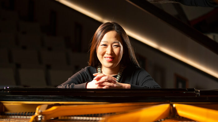 Minju Choi Witte peers through the open top of a grand piano