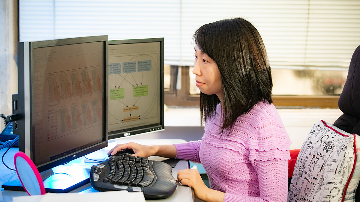 Xiaomin Qiu sits in front of her computer studying data